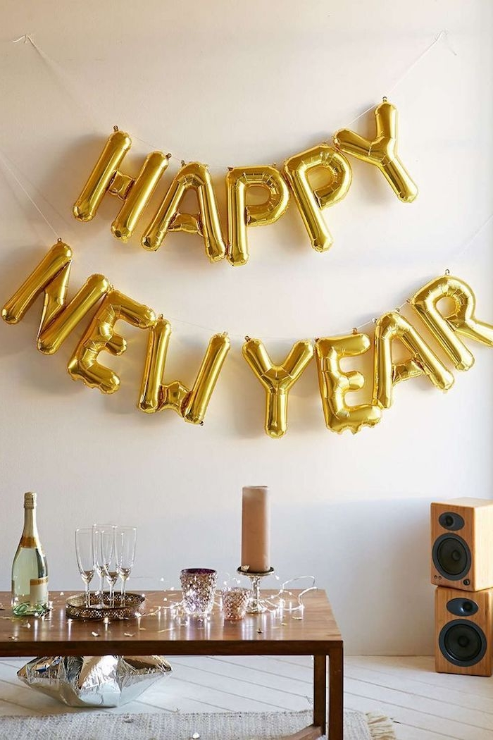 ballon en lettres bonne année en or, table basse de bois et deco de guirlande lumineuse, ballon en forme d etoile argenté