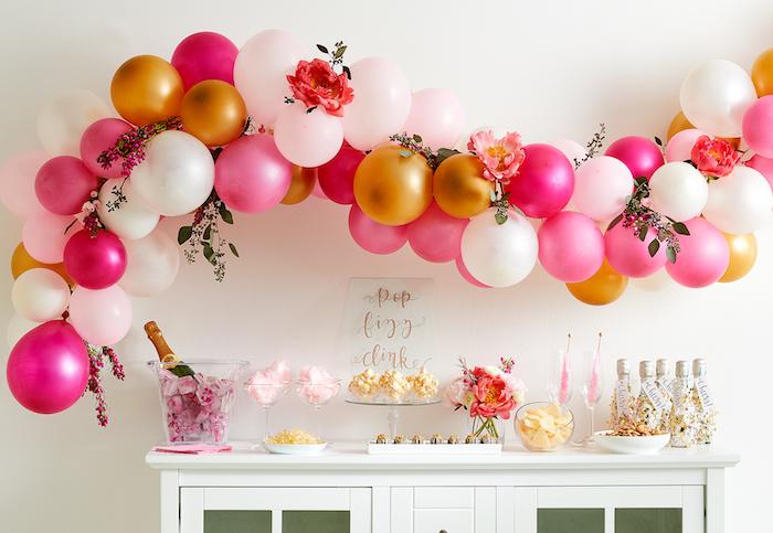 arche de ballons couleur blanc, or et rose au dessus d un buffet blanc avec candy bar barbe à papa, po corn, thème soirée cirque