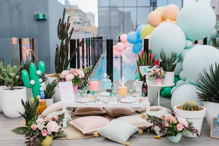 thème soirée bohème chic sur la terrasse, ballons de couleurs pastel et tailles variées., table basse blanche et coussins boheme chic par sol