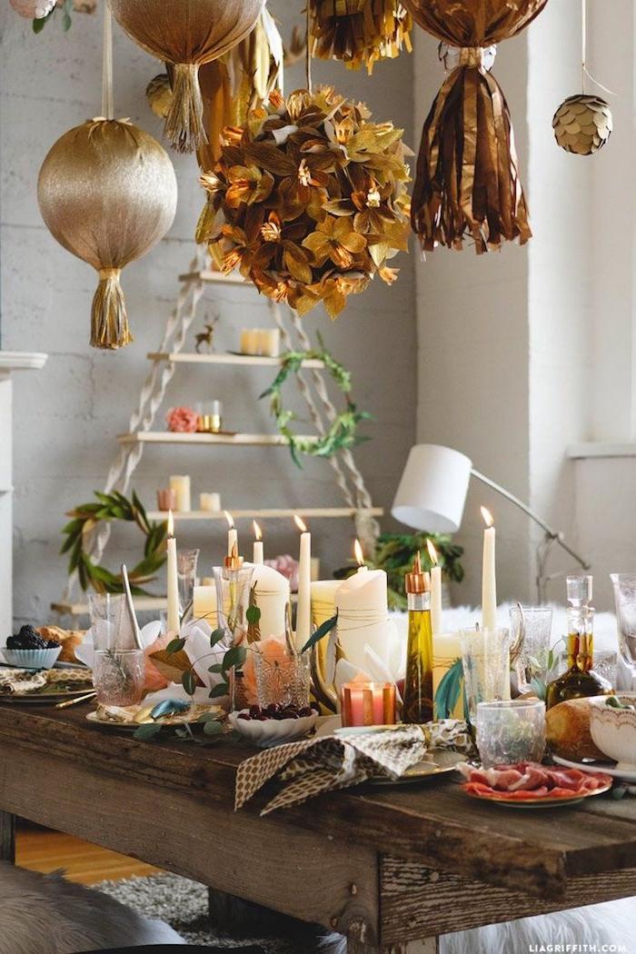 deco boheme chic de table rustique avec bougies et vegetation decorative, suspensions en or, étagère bois et accents deco hippie