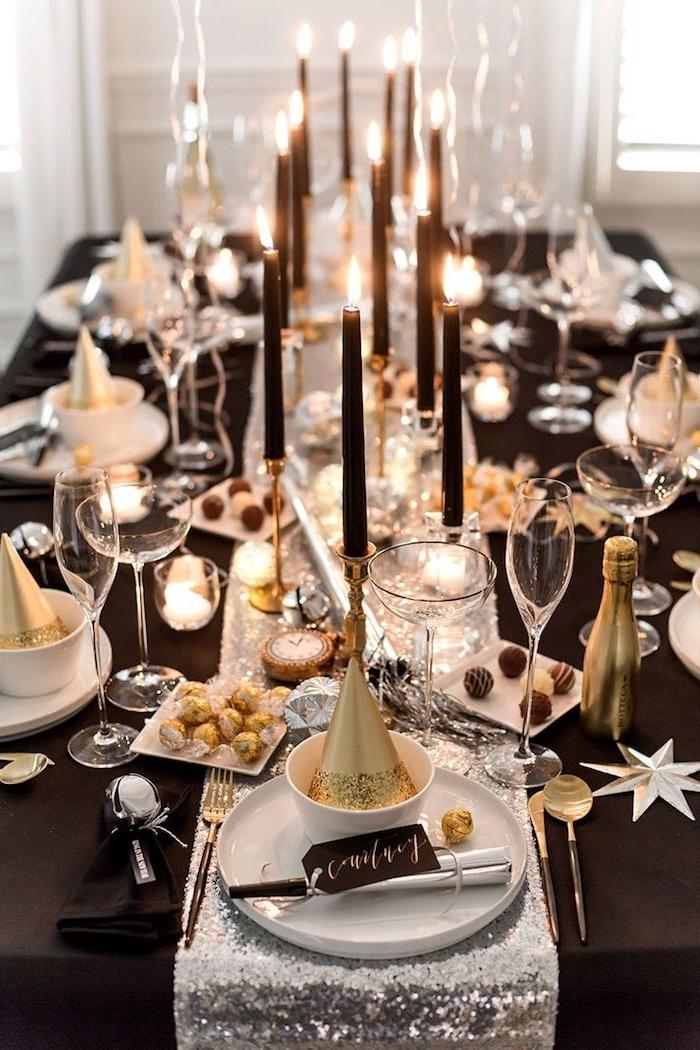 table décorée de nappe noire et chemin de table argenté, bougies noires sur chandelles or, deco noir blanc et or elegante