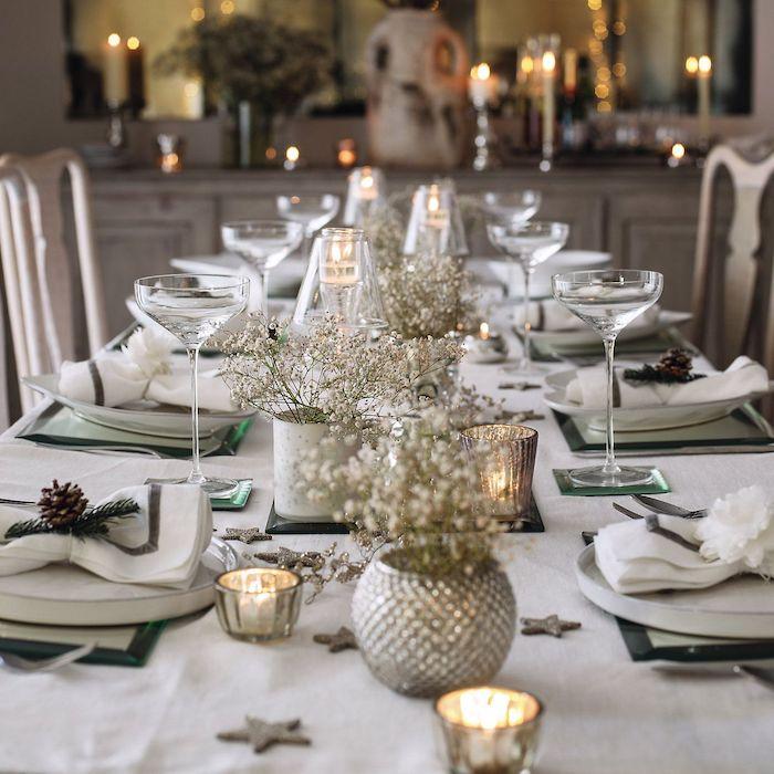 nappe blanche avec petits bouquets de fleurs blanches dans mini vases, serviettes décorées de pomme de pin et brins de pin