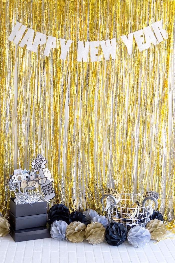 rideau à franges or pailletées, inscription lettres bonne année, fleurs de papier sur sol blanc, deco bonne année
