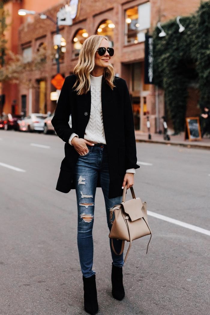style vestimentaire femme au travail en jeans déchirés combinés avec sweat femme marque de couleur blanche et manteau noir