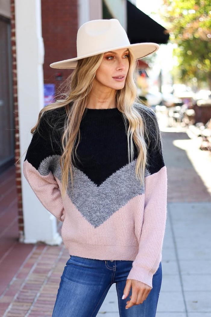 look chic en pull de marque femme de couleurs noir gris et rose pastel combiné avec paire de jeans foncés et capeline blanche