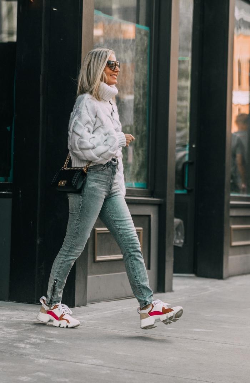 tenue casual chic en pull torsadé femme de couleur blanche combiné avec jeans foncés et paire de basket blanc et rouge