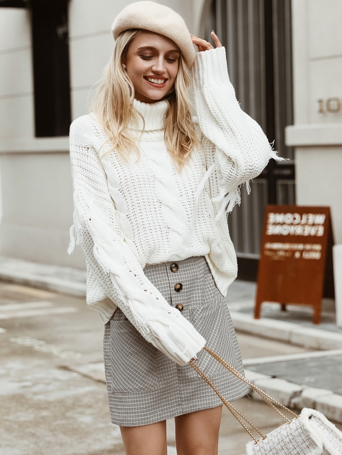 vision chic et stylée pour l'hiver en pull-over à col roulé blanc à design torsadé combiné avec jupe courte gris clair