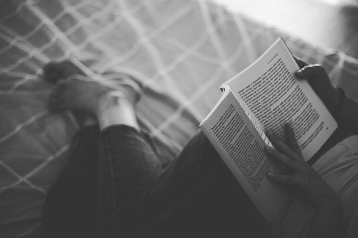 Livre photo noir et blanc, symbolique des couleurs noir et blanc, femme au lit avec un livre dans les mains