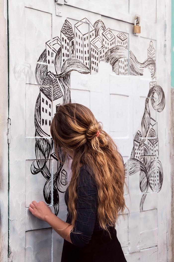 Robe noire manche longue, idée coupe cheveux long, coiffure ondulée tendance pour femme moderne, photo femme qui dessine