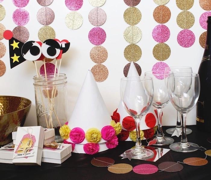 guirlande de cercles pailletés piur decorer un mur, chapeaux de papier décorés de fleurs de papier coloré, lunettes photobooth, soiree a theme