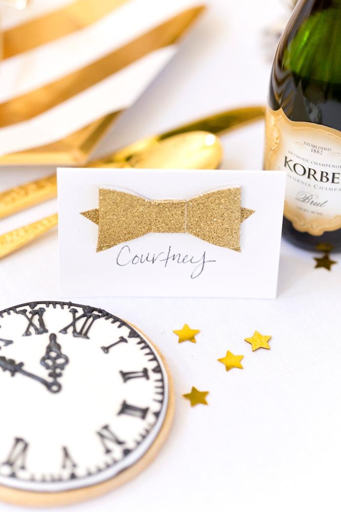 marque place nouvel an en noeud de papillon de papier doré, sablé à motif horloge nouvel an, couverts et assiettes or et blanc