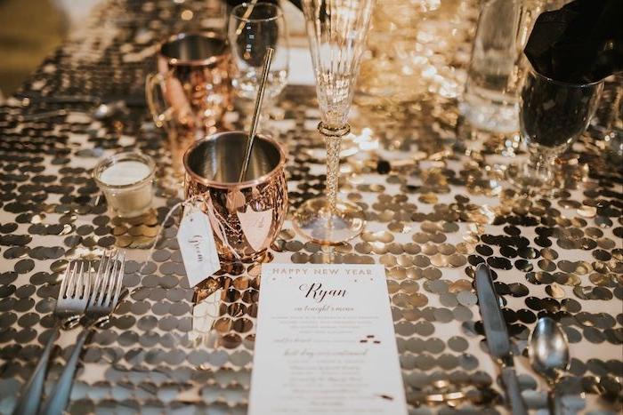 deco table nouvel an à détails de table couleur or metallique, bougies decoratives et verres rose gold, couverts en argent