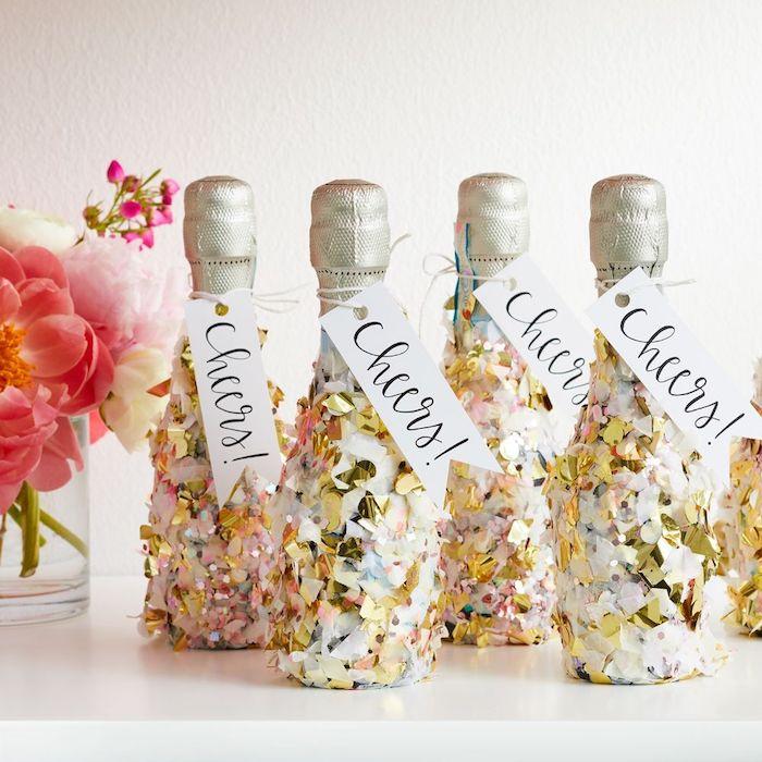 mini bouteilles de champagne décorées de confettis avec étiquette santé. petit bouquet de fleurs, decoration nouvel an 2020