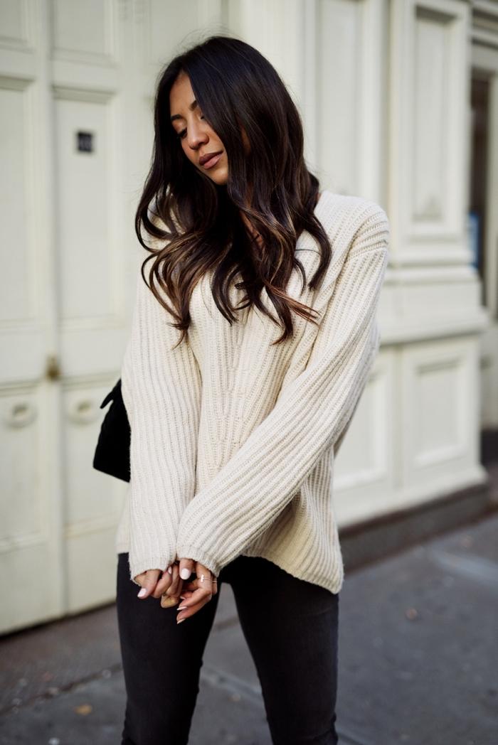 tenue confortable et chic pour l'hiver en pull blanc oversize combiné avec pantalon slim noir et sac à main noir