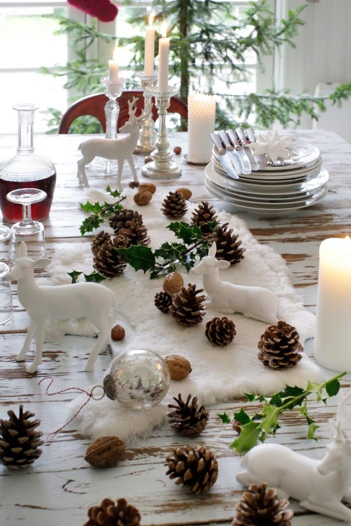 créer une déco de table cozy avec tapis blanc décoré de pommes de pin et figurines animalières, les plus belles tables de noel