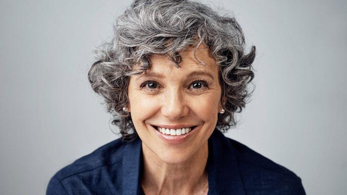 coupe de cheveux gris femme 60 ans aux cheveux bouclés avec volumes, boucles d oreilles en perles
