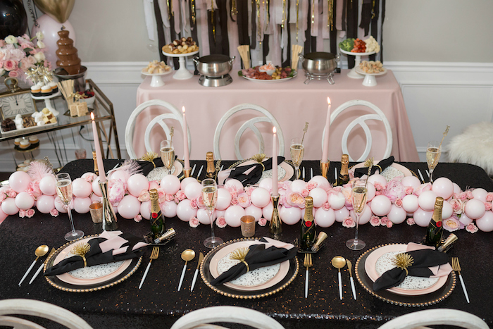 deco jour de l an avec centre de table de ballons roses et fleurs, nappe table noire, serviette noire et bougies roses dans chandails en or