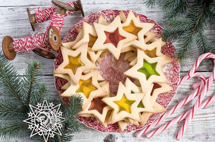 biscuit eoile de noel au beurre et sucre avec centre gélifié rouge, vert et jaune dans une assiette, recette biscuit sablé