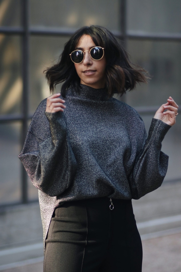 vision femme stylée en pull de marque élégante de couleur noire combinée avec jupe longue à taille haute et lunettes de soleil
