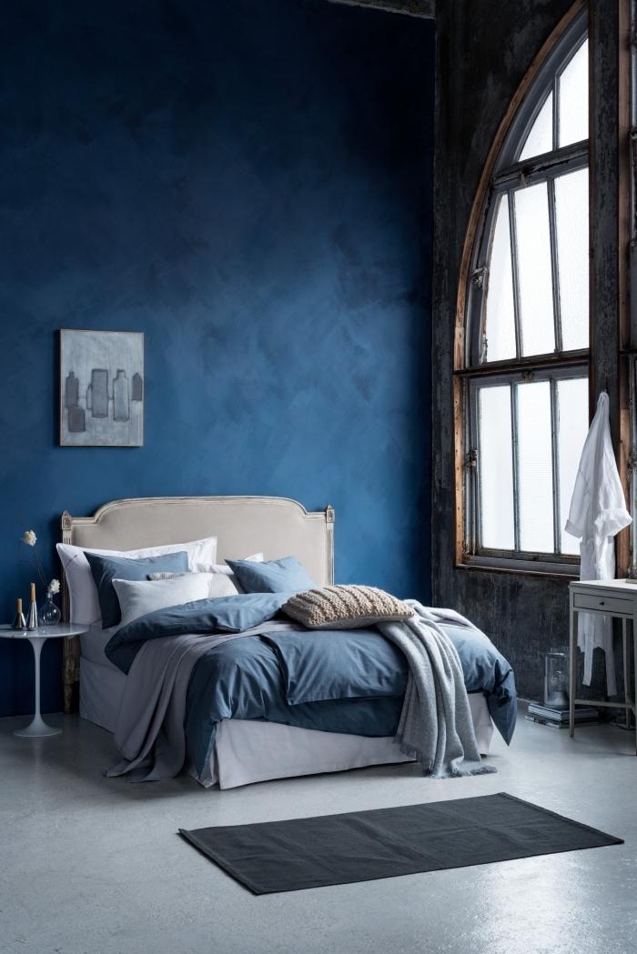 peinture de couleur bleu marine dans une pièce à haut plafond avec sol gris et meubles en blanc, idée déco chambre aux murs sombres