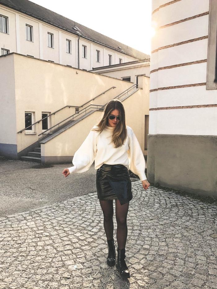 look femme chic avec jupe courte à coupe asymétrique en simili cuir noir et pull-over loose à col roulé blanc
