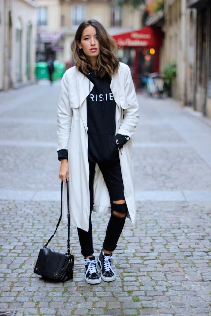 Manteau blanc long, jean noir déchiré, sac débardeur noir cuire, style streetwear femme, tenue swag hip hop street style