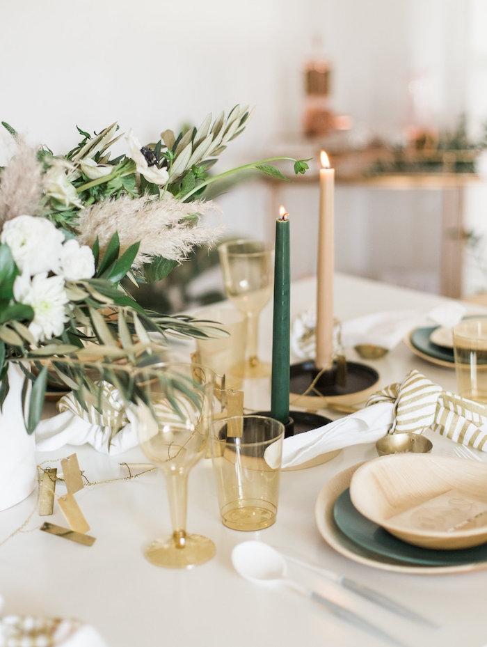 centre de table deco vegetale avec des verres en plastique, bougies vert et blanc cassé sur nappe blanche, assiettes de couleurs variées