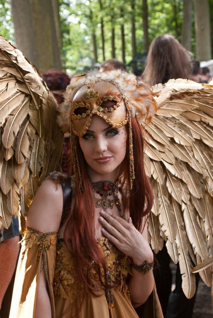 Belle femme en robe épaules dénudées avec manches longues fendues, ailes dorés costume avec masque vénitienne