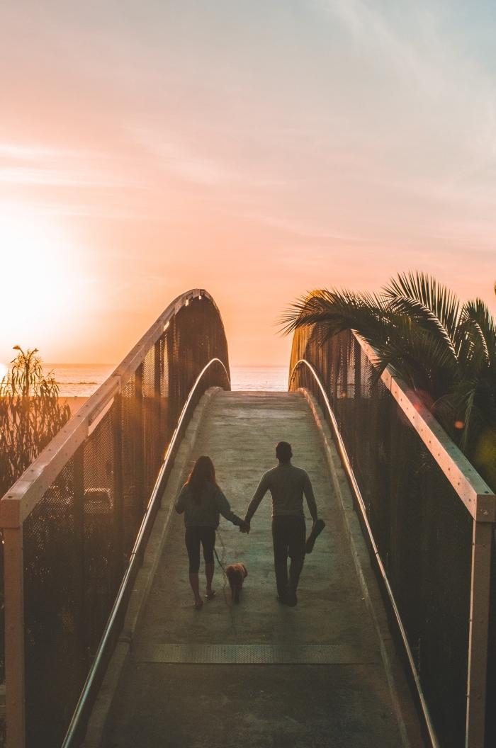 idée d'activite a faire a 2, couple amoureux avec leur chien en promenade au bord de la mer au coucher de soleil