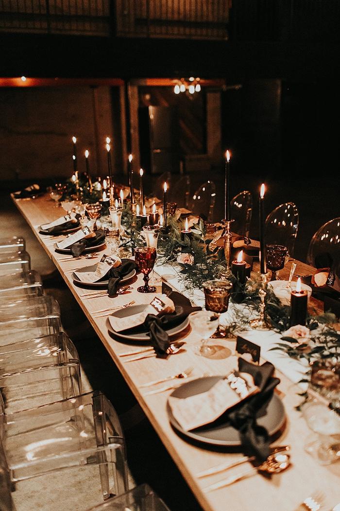 theme de mariage romantique, lumière tamisée provenant de bougies décoratives originales, centre de feuillages et fleurs chaises en verre