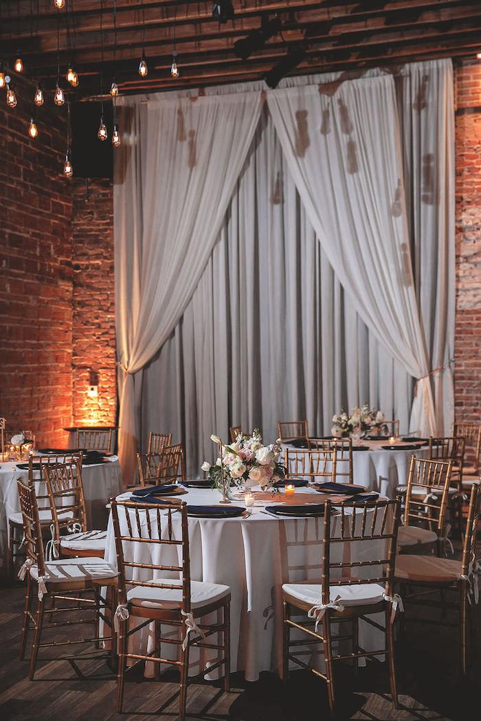 theme de mariage industriel dans vieille usine, ampoules electriques, chaises bois et blanc, tables décorées de nappes blanches
