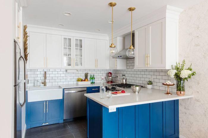 meuble bas et ilot central bleu et plan de travail blanc, credence carrelage blanc, meuble haut blanc, suspensions et robinetterie laiton