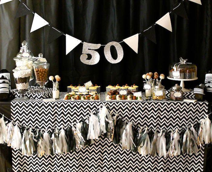 guirlande fanions et lettres 50 ans, idee deco de table anniversaire nappe motif chevron, candy bar bonbons, petits gateaux, fond noir