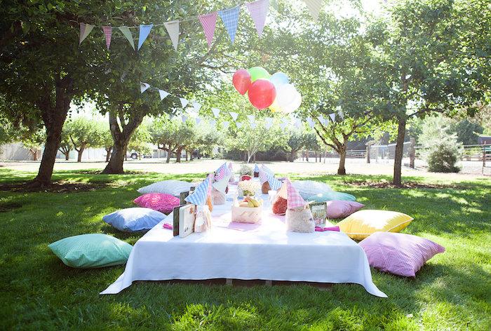 decoration pour anniversaire pc nique en plein aur, table basse avec nappe blanche et serviettes et coussins colorés pat sol