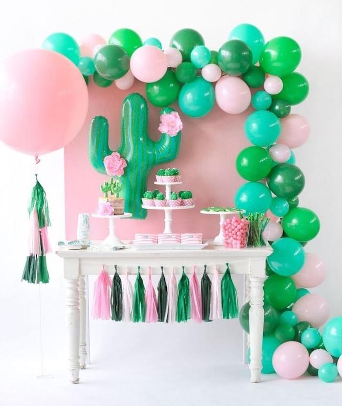 ballons d anniversaire en rose et vert et mur de fond rose, guirlande de pompons rose et vert, idee deco cactus soirée à thème, candy bar anniversaire original