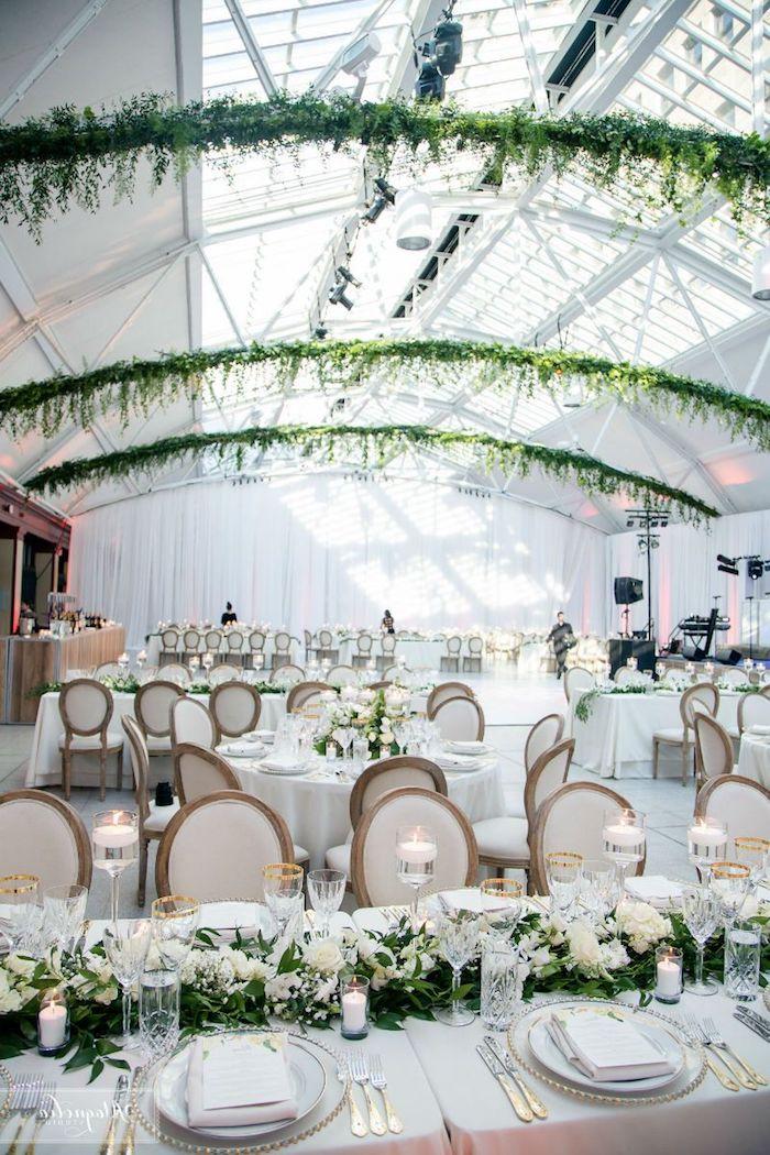 arche de feuillages en hauteur, table décorée de nappe blanche et centre de feuillages et fleurs blanches, bougies blanches, couvets or