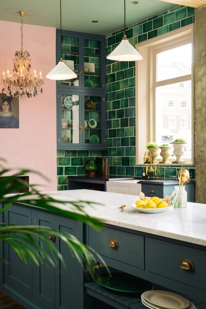 comment aménager une cuisine moderne de style tropical avec pan de mur rose et meuble de couleur vert de gris