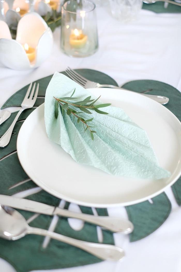 décoration de table naturelle en couleur blanc et vert avec couverts en argent et bougies, idée de pliage serviette rapide en forme de feuille