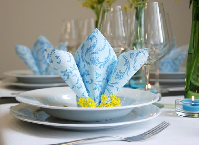 arrangement de table avec bouquets de fleurs fraîches et serviette pliée à motif fleuris, déco de table festive