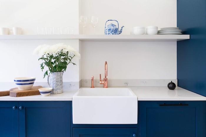 meuble bas bleu nuit et plan de travail marbre blanc, étagère blanche ouverte dans une cuisine pantone bleu et blanc, robinet cuivre
