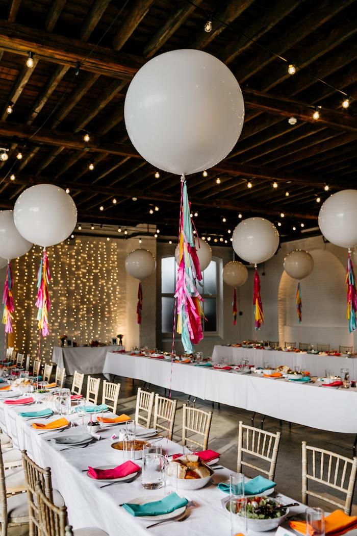 ballons blancs à l hélium avec décoration de chutes de papier coloré au dessus de table à nappe blanche déc0rée de serviettes multicolores
