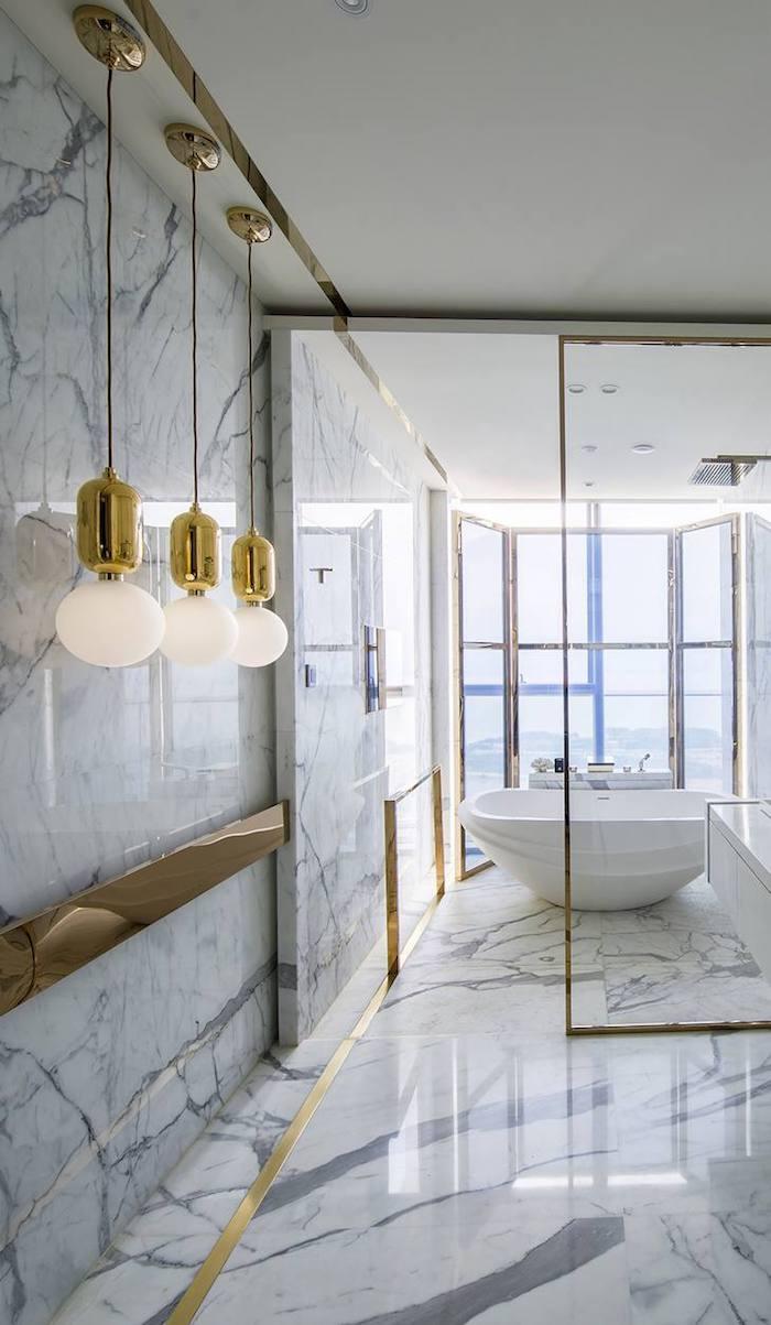 Salle de bain marbre blanc avec gris, chouette idée pour la salle d'eau accessoirisé en or, baignoire avec vue de la ville