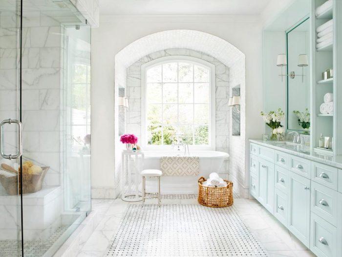 Arche de fenêtre qui donne de lumière de jour, vase avec fleurs, meuble de rangement bleu claire, modele salle de bain, idée stylée salle d'eau et cabinet de toilette