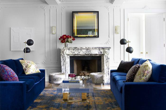 cheminée de marbre dans un salon blanc avec canapés bleu marine, table basse en verre transparente sur tapis or et bleu, lampes noires