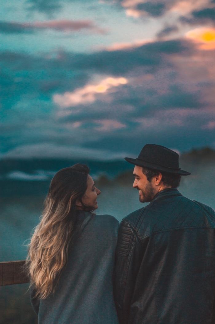 activités à faire en couple, photo romantique d'un couple amoureux devant le coucher de soleil au bord de la mer
