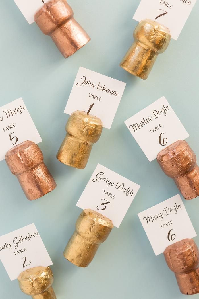 marque place mariage originale, idee diy pour recycler des bouchons de liège colorés de peinture or avec étiquette numéro de table