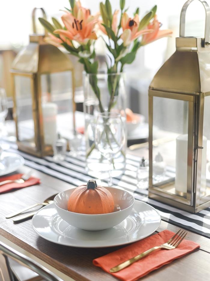 arrangement de table avec vases de fleur oranges et lanternes à bougies dorées, idée de pliage serviette orange en deux