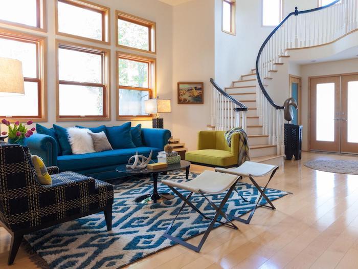 canapé bleu dans un grand salon avec tapis bleu et blanc, table basse pied noir et verre, parquet clair, murs blancs et cadres de fenetre bois