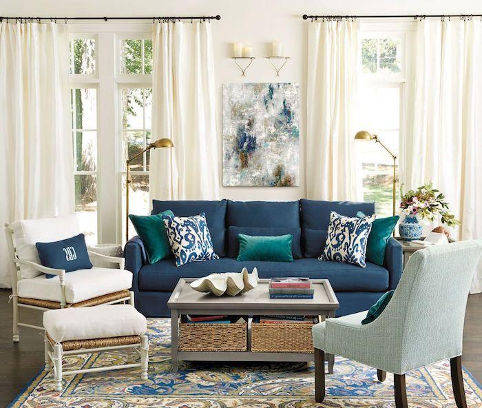 canapé bleu nuit dans un salon blanc aux accents laiton, tapis coloré oriental sur parquet bois foncé