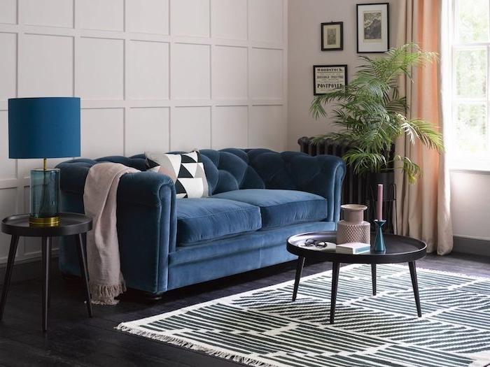 canapé bleu nuit dans un salon blanc aux rideaux peche clairs, parquet bois foncé avec tapis zèbre et table basse noire